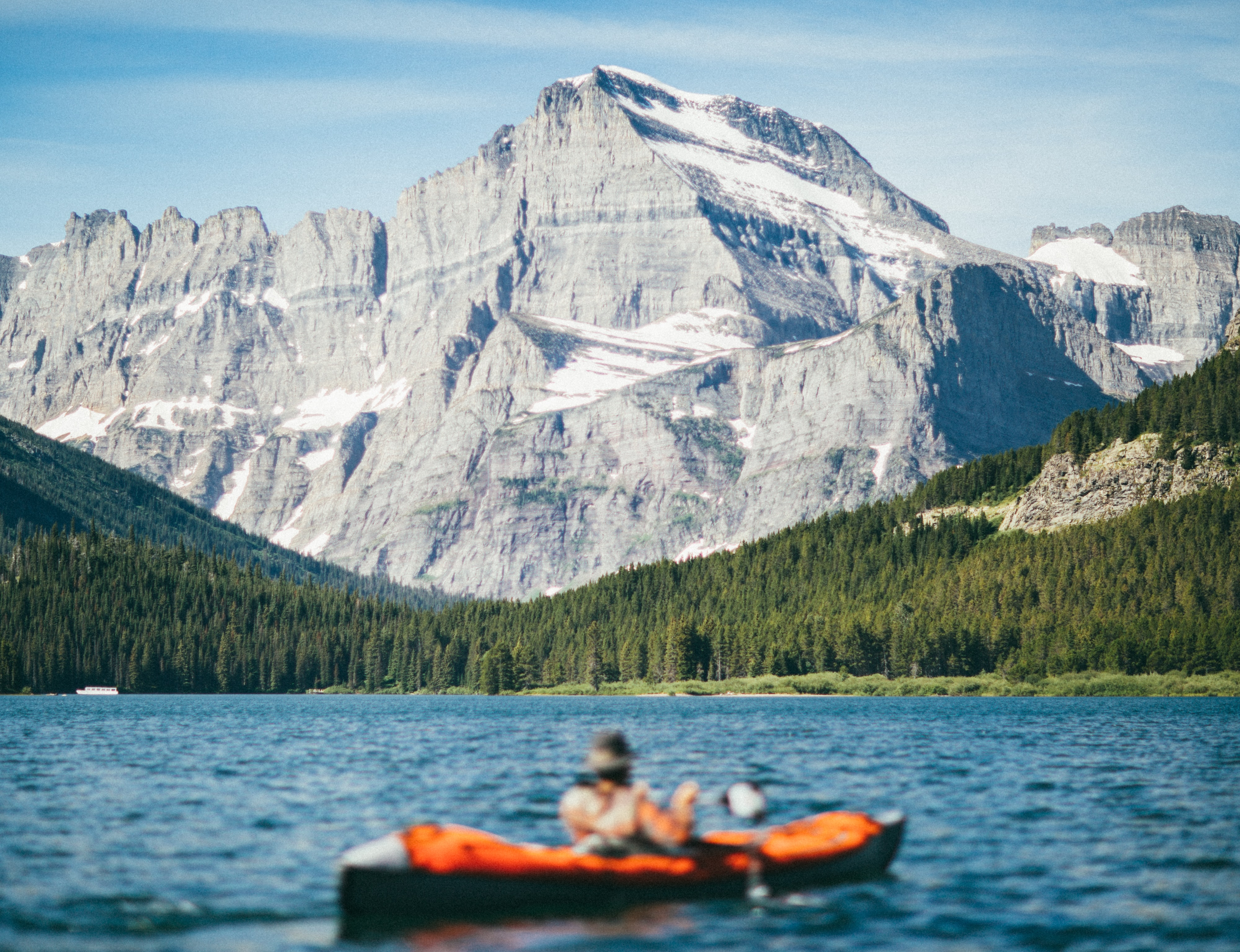 A person kayaking by the mountains in Swiftcurrent Lake