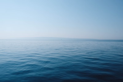 body of water under blue and white sky at daytime sea teams background