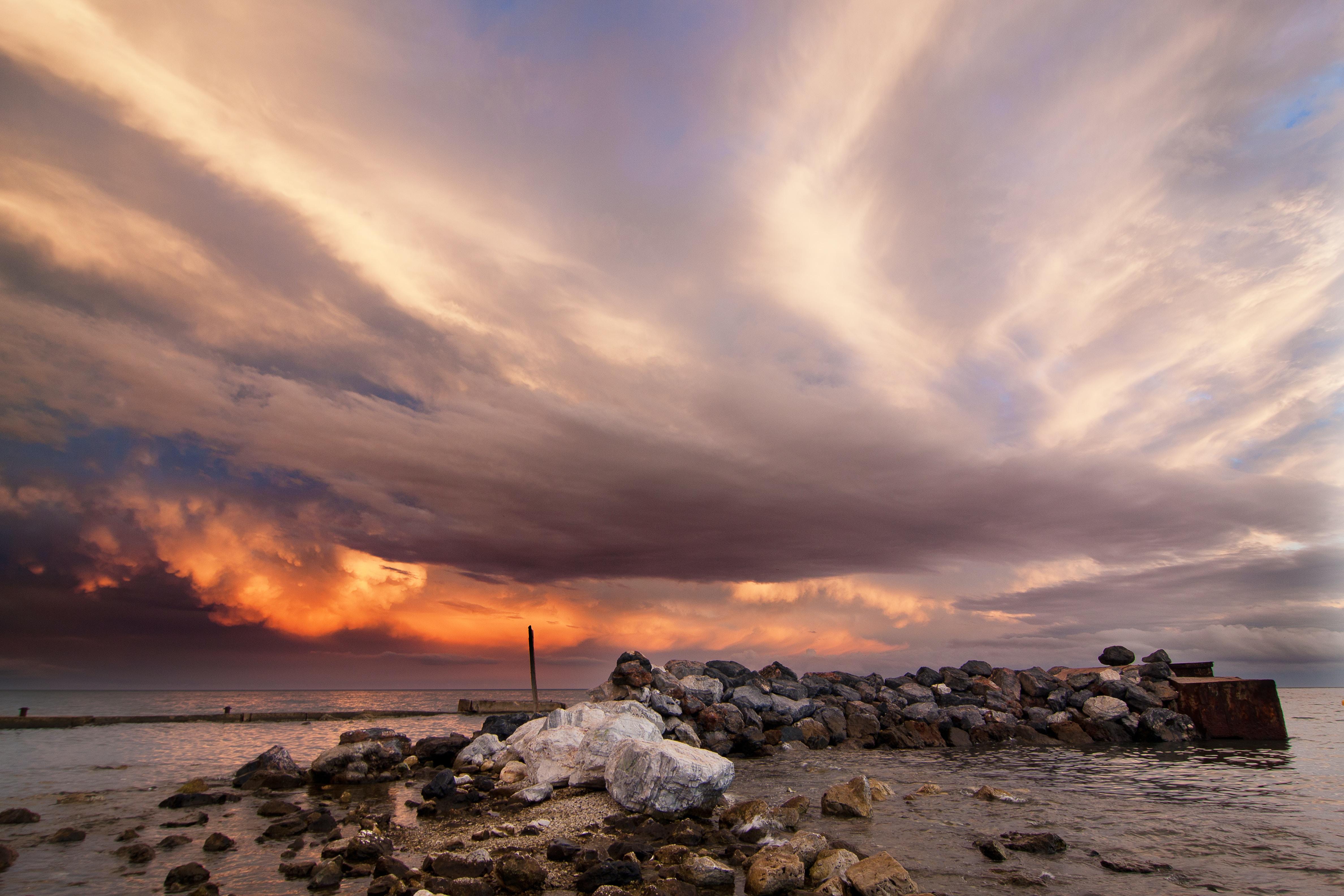 pile of stones near seashore under cloudy sky