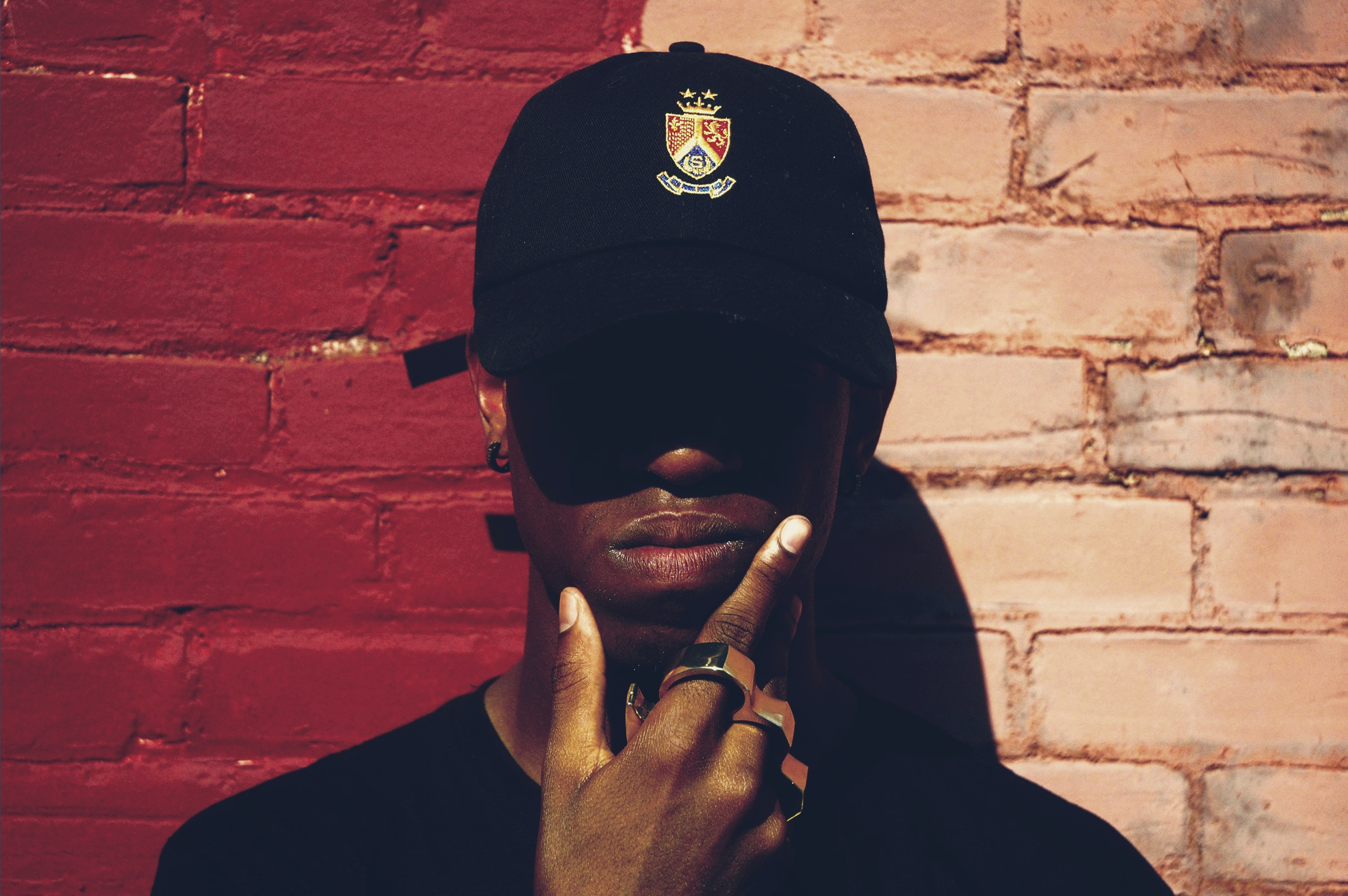 A man wearing a baseball cap, brass knuckles and earrings holding his chin by a brick wall