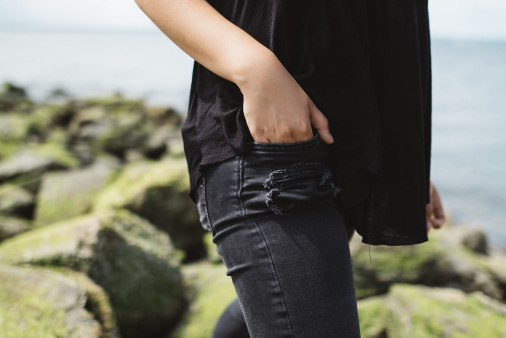 person wearing black denim bottoms near on body of water during daytime
