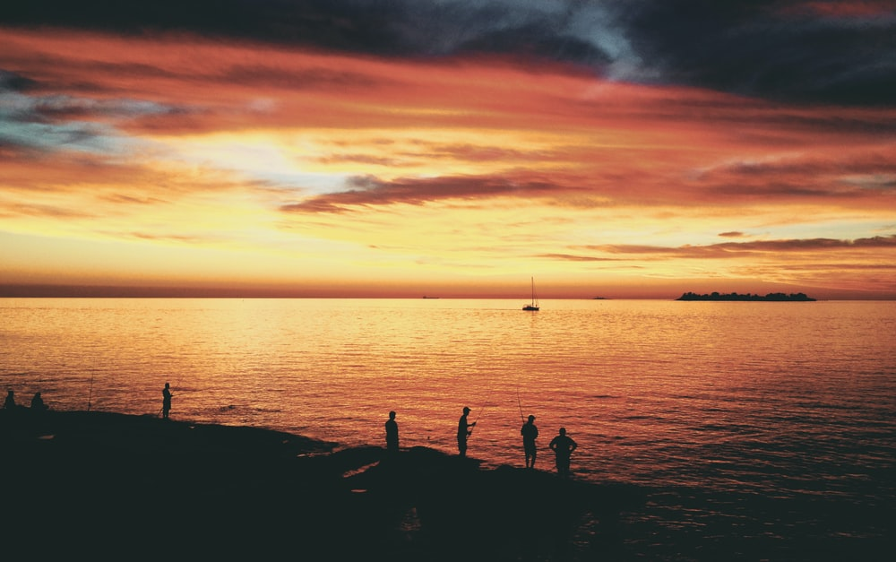 silhouette photo of people near seashore during sunset