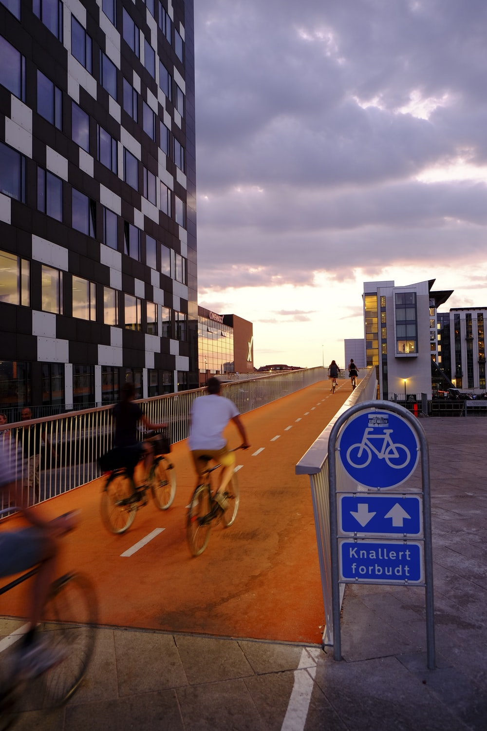 people riding bicycles inside bicycle lane beside skyscraper