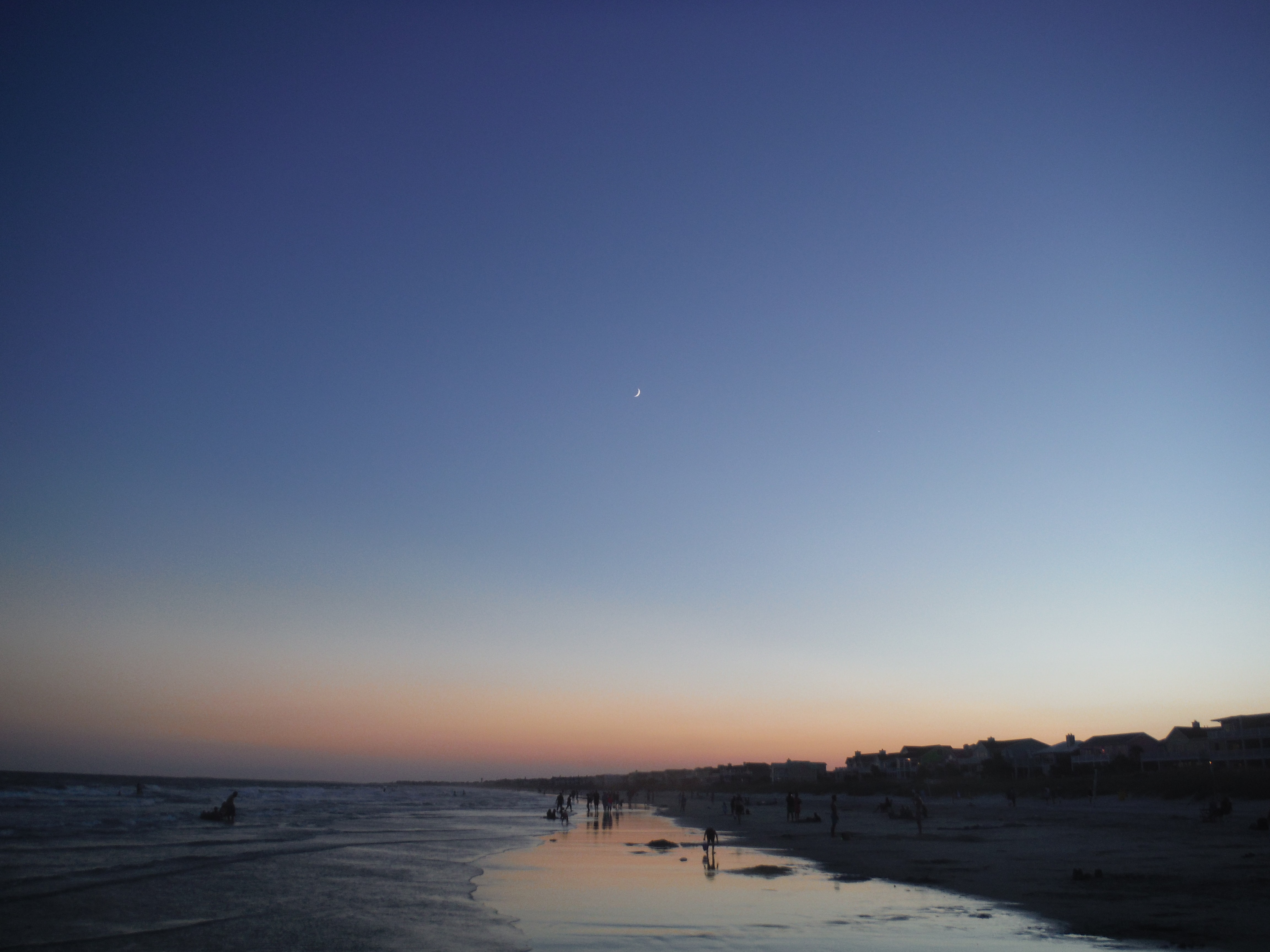Night falls over a beach as a crescent moon shines in the sky