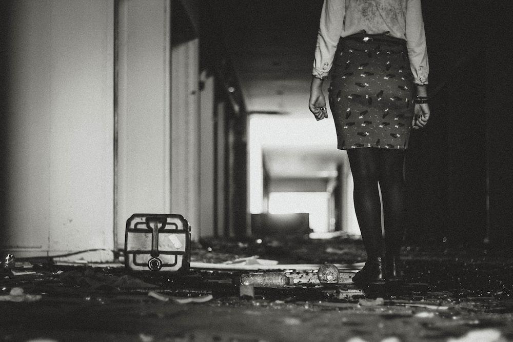 woman wearing skirt beside white building