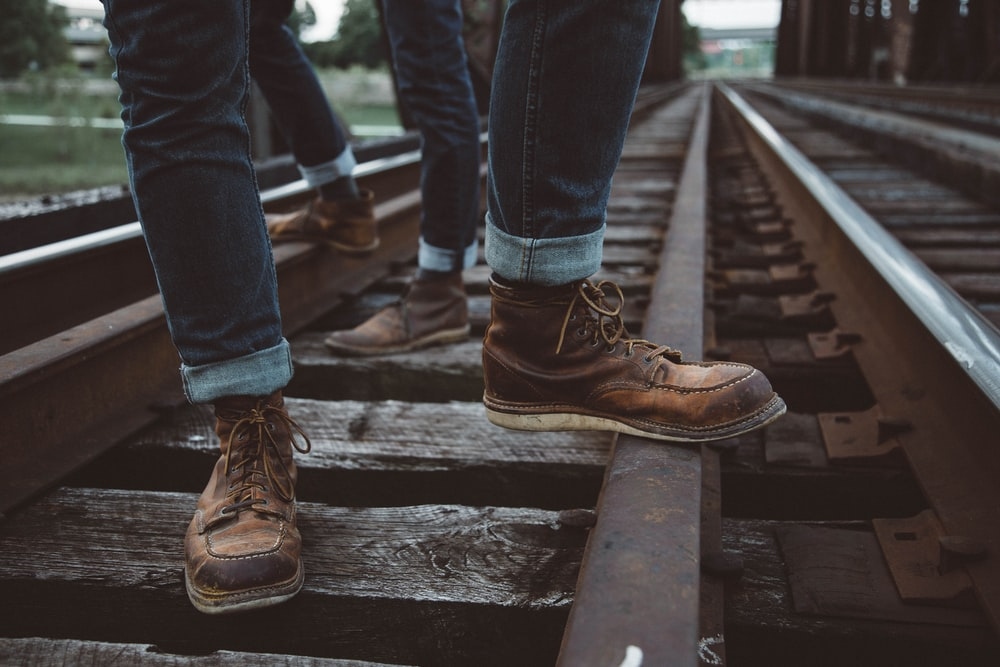two people wearing brown shoes standing in train rail