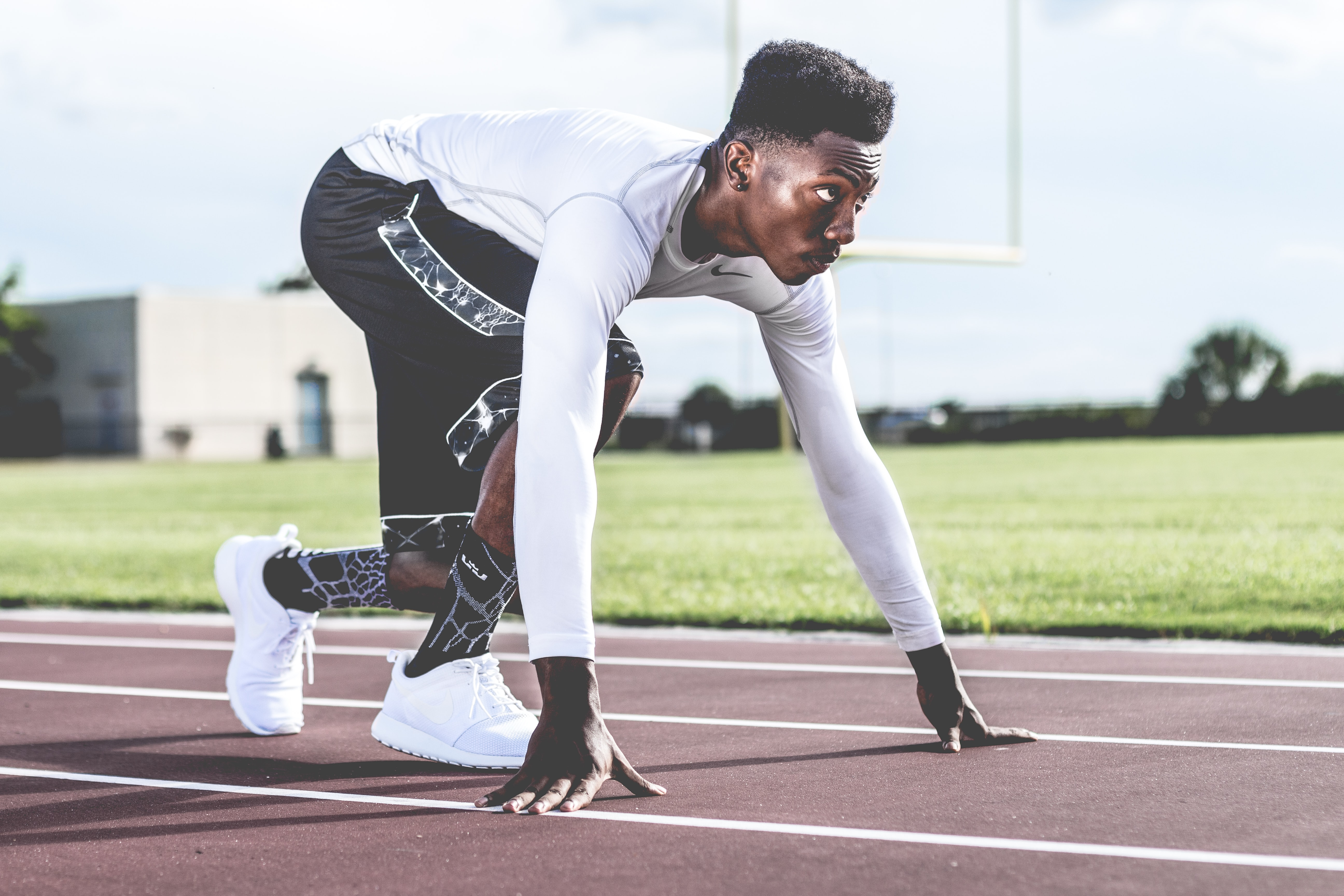 man ready to sprint on field track