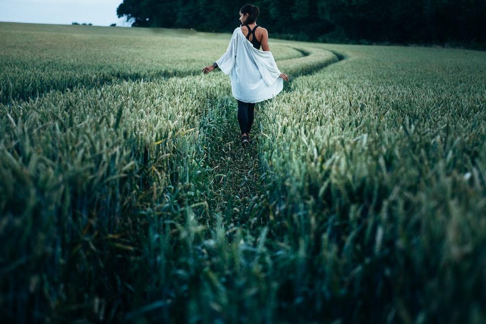 woman walking on grass field
