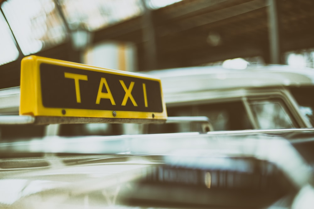 black and yellow Taxi signage