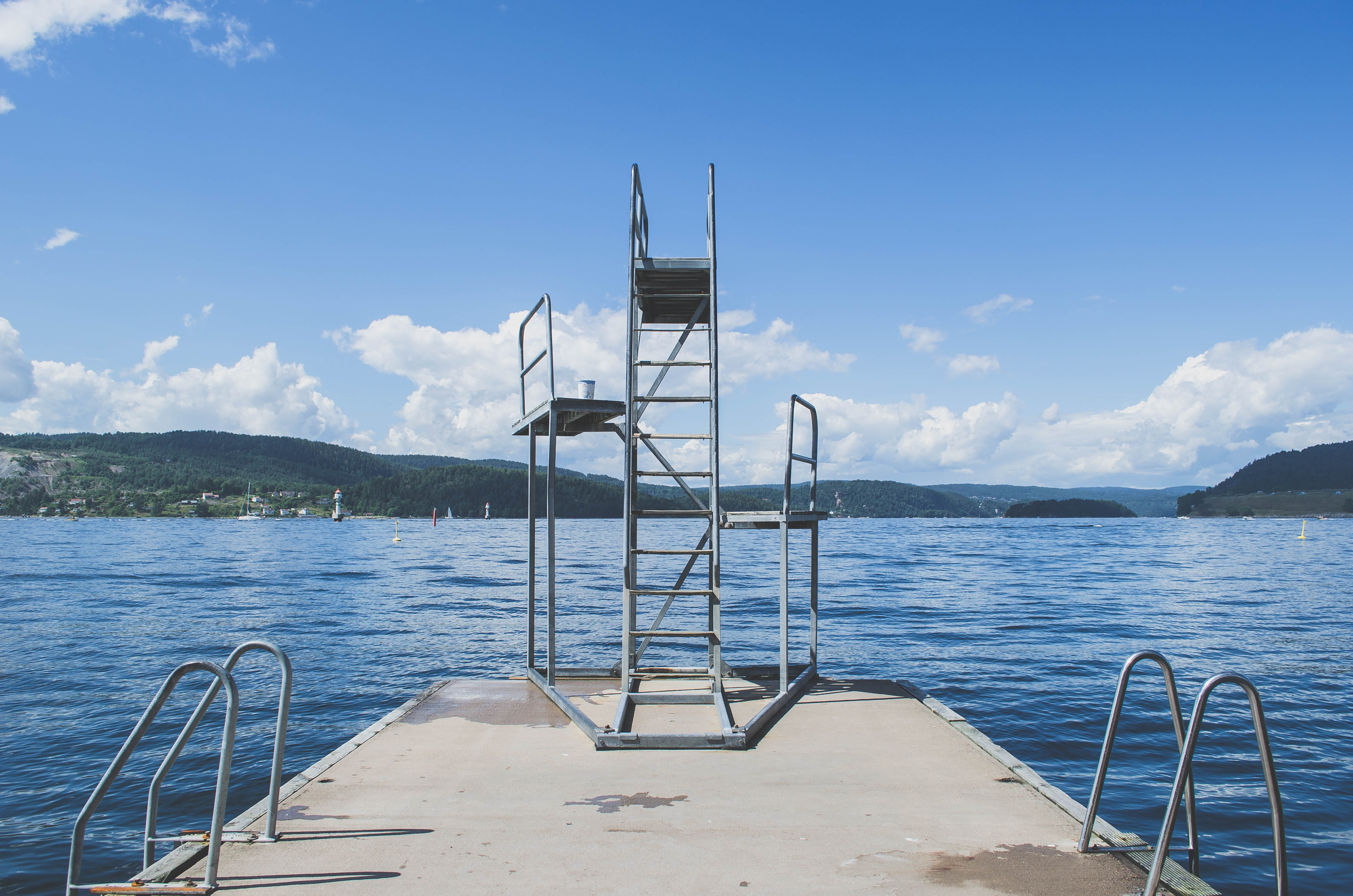 A pier with ladders a diving board on a tranquil lake