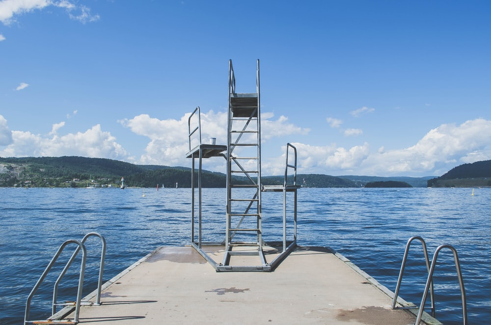 gray diving platform near water