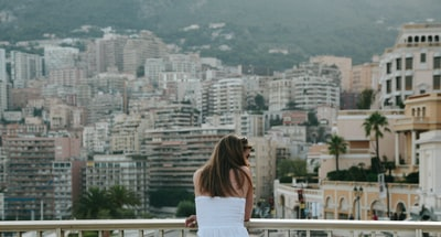 woman standing beside railings looking on her right monaco teams background