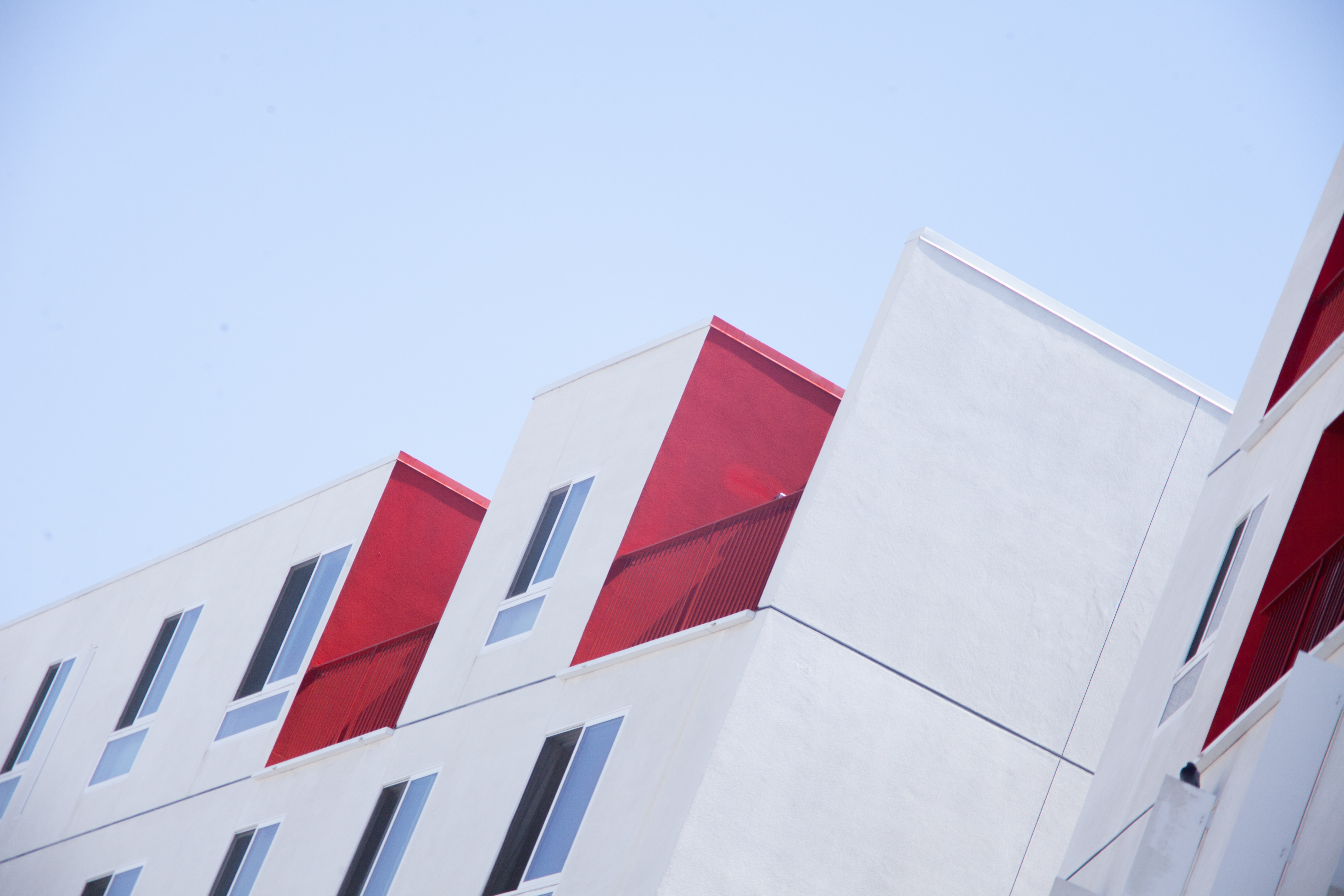A white residential building facade with red balconies in Los Angeles