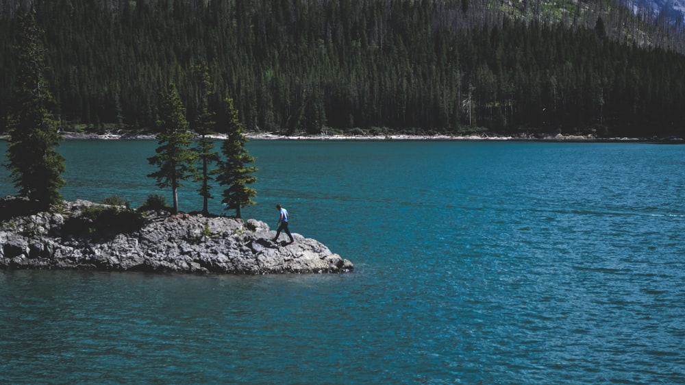 person walking on rock beside body of water
