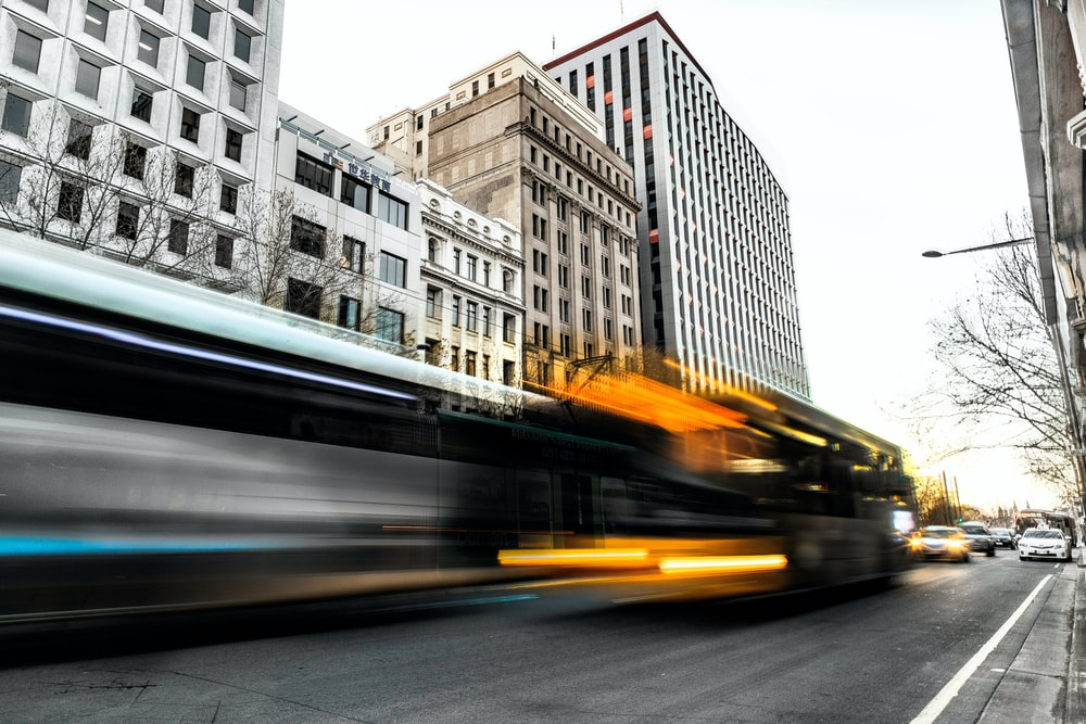 A long-exposure shot of long bus and trolley silhouettes on a city street