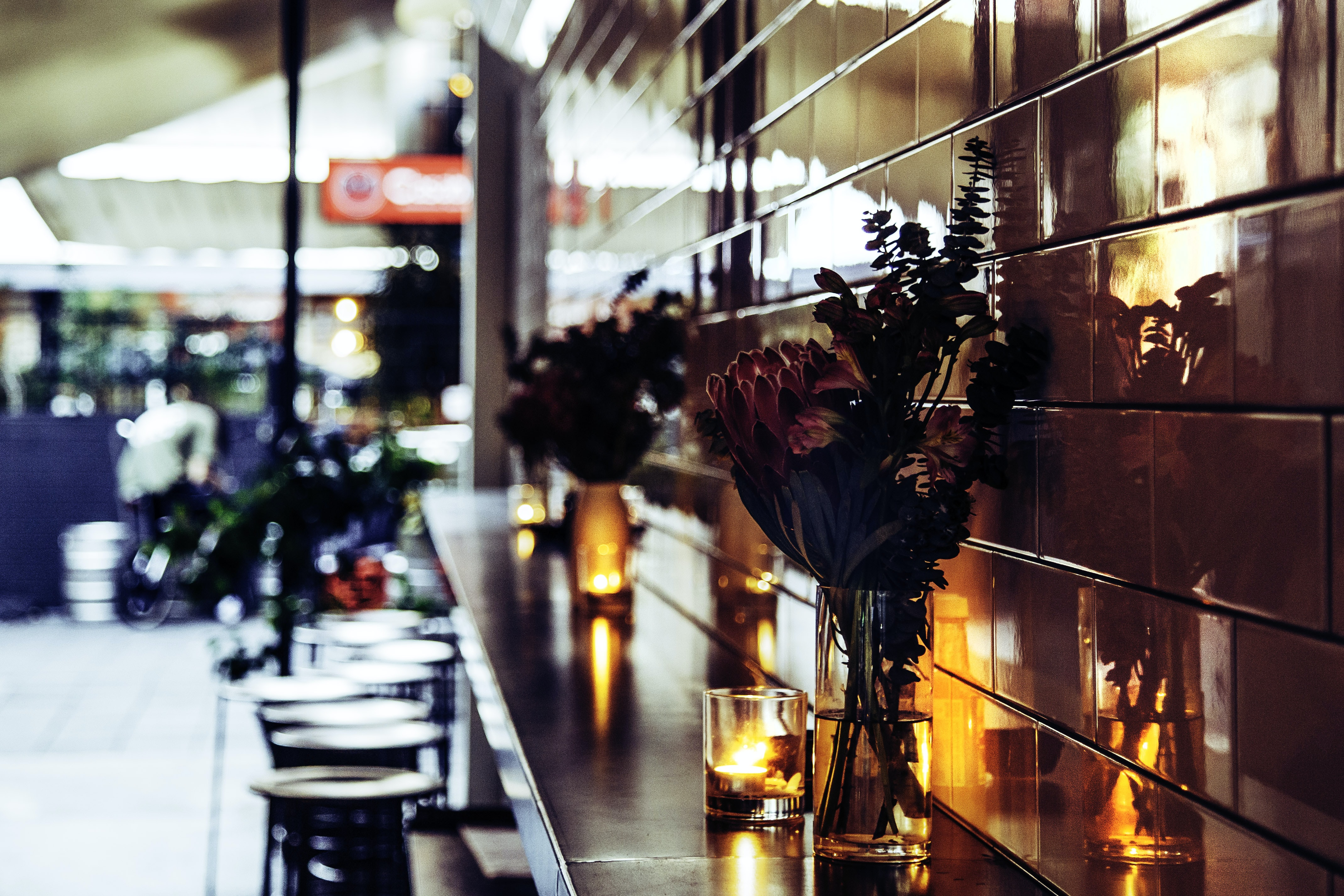 Empty bar stools near a wall ledge with candles and flowers in vases on it