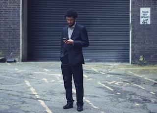 man in black formal suit using smartphone