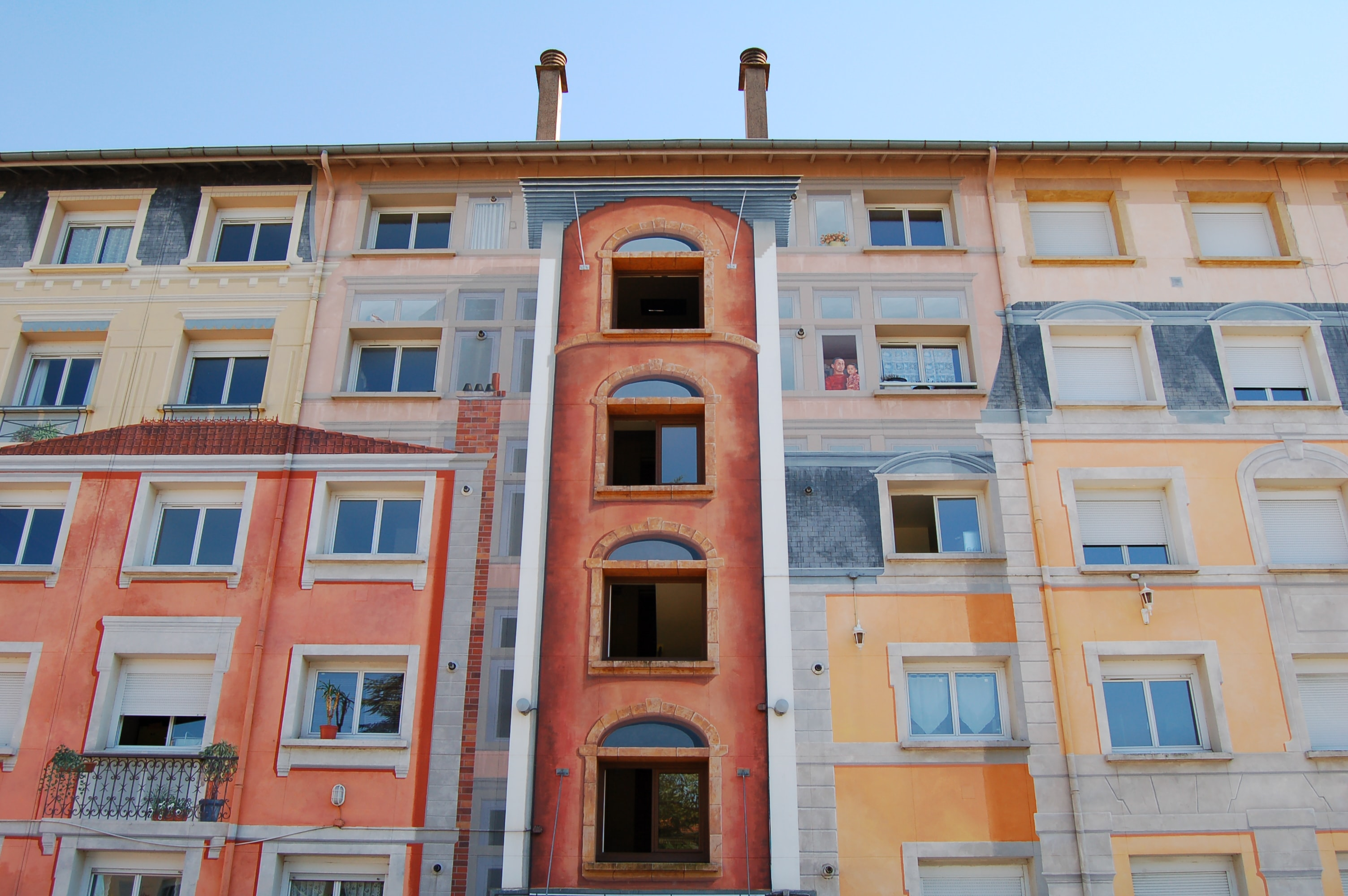 Blue sky and urban building in Lyon with multicolored walls and complex facade with varied windows