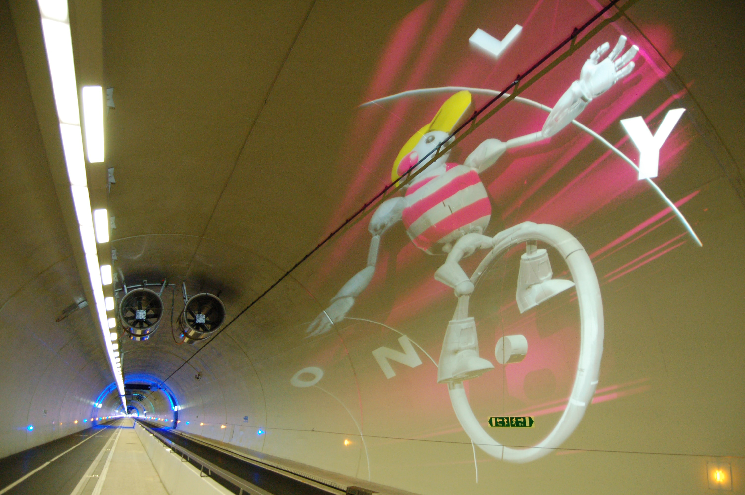 A white character on a unicycle displayed on the ceiling of a tunnel.