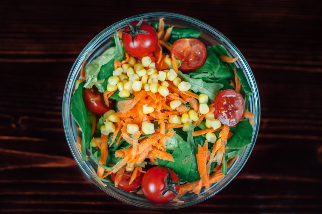 Bowl of fresh salad with corn, carrots, tomatoes, and spinach