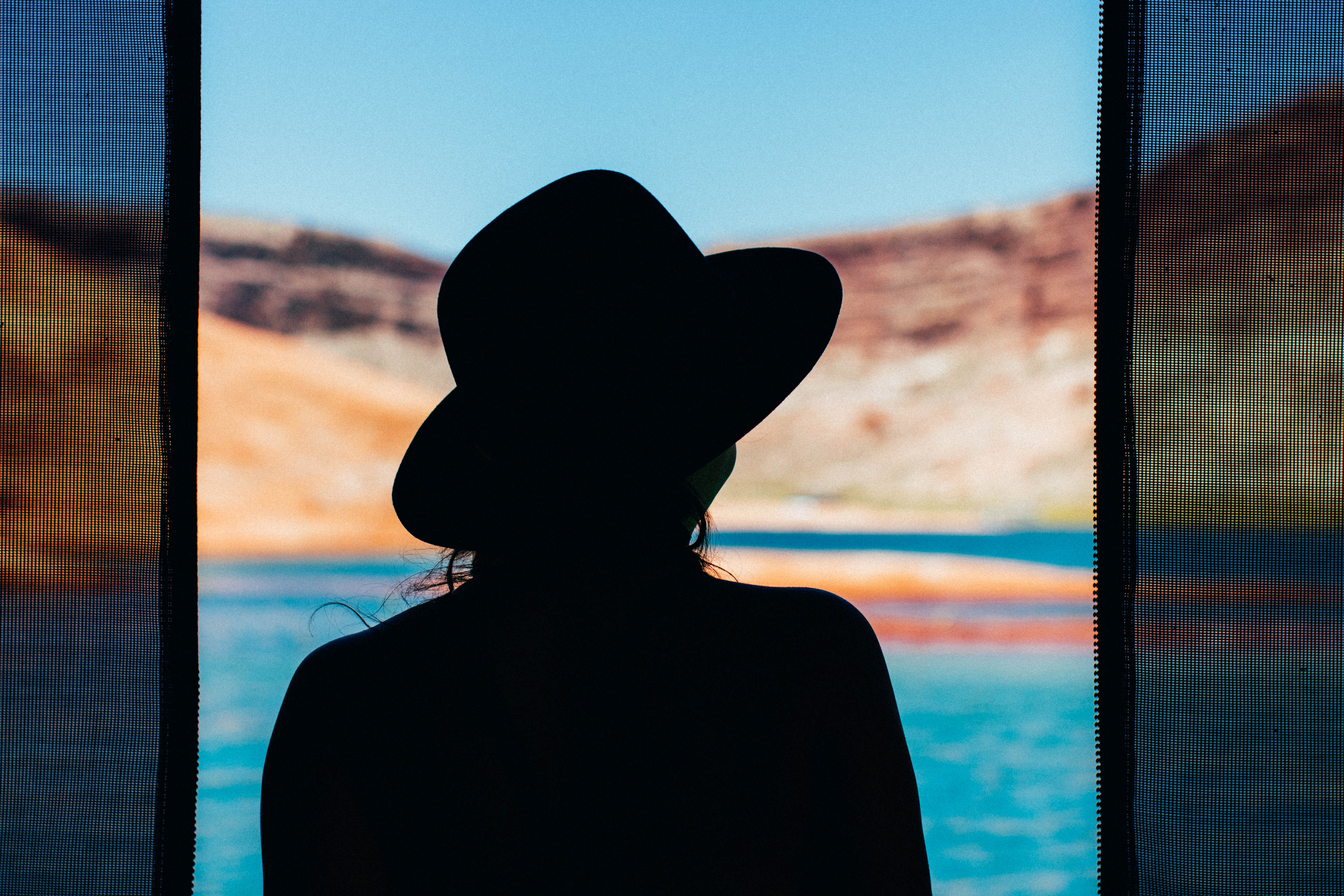 Silhouette of a woman in a hat between curtains looking at the water in Lake Powell