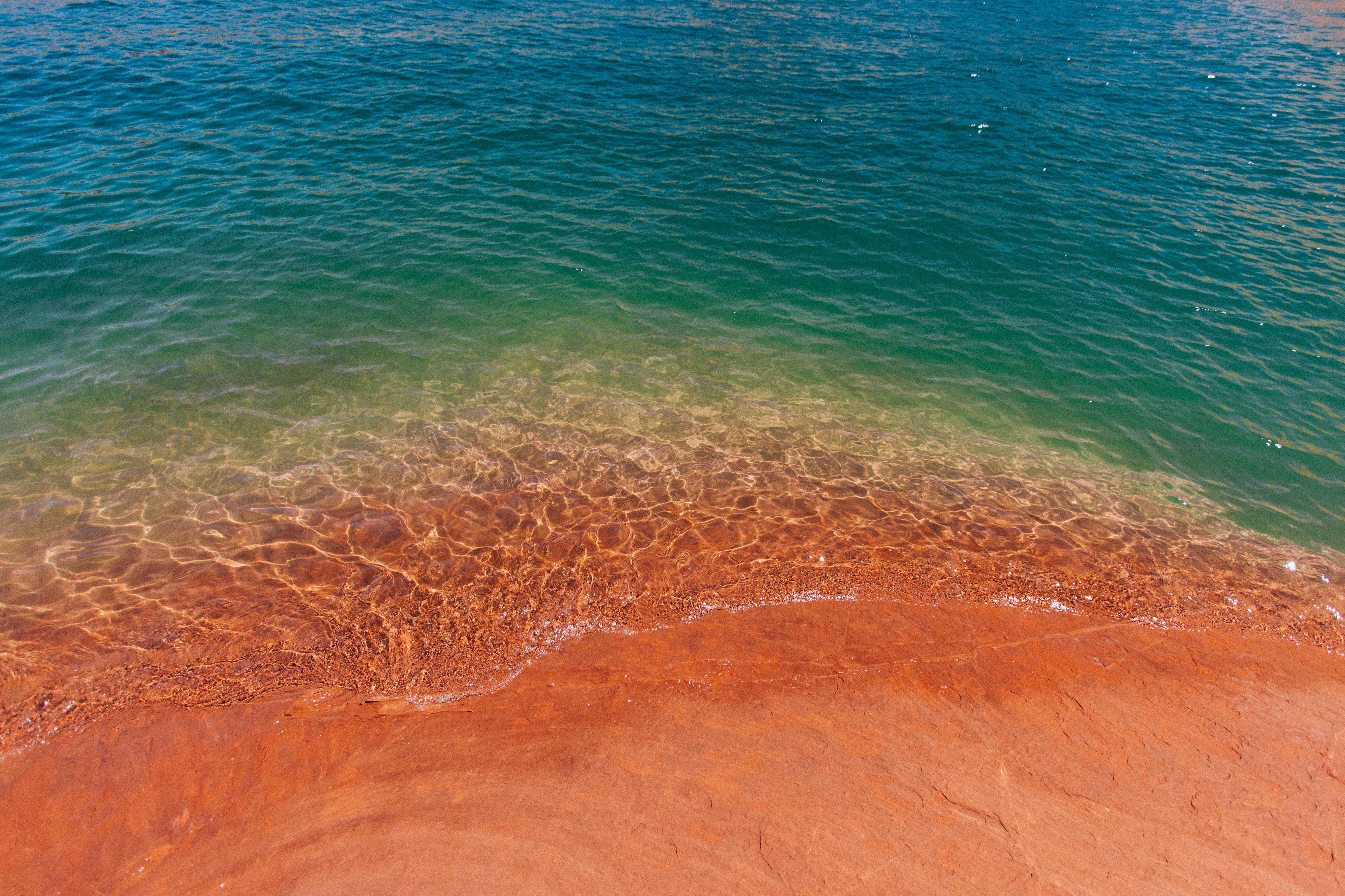 Drone view of the ocean washing on the red sand shore at Lake Powell