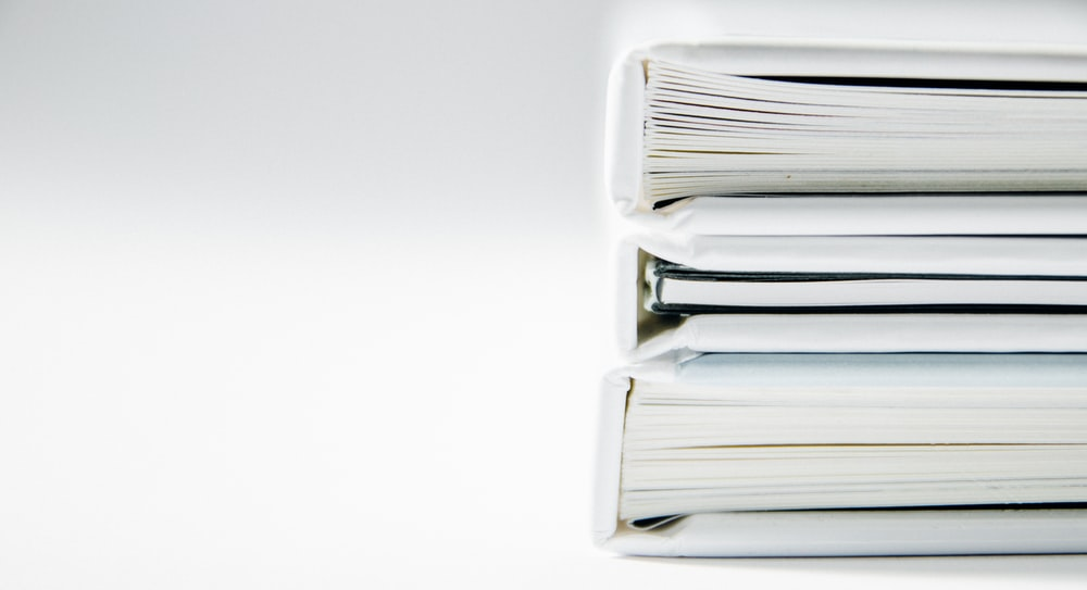 A stack of thick folders on a white surface