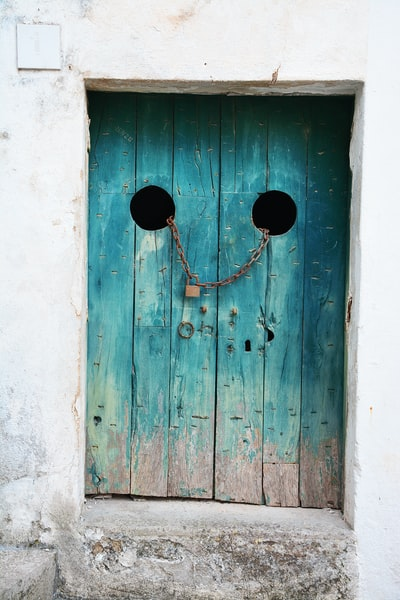 teal wooden door with gray chain and brown padlock