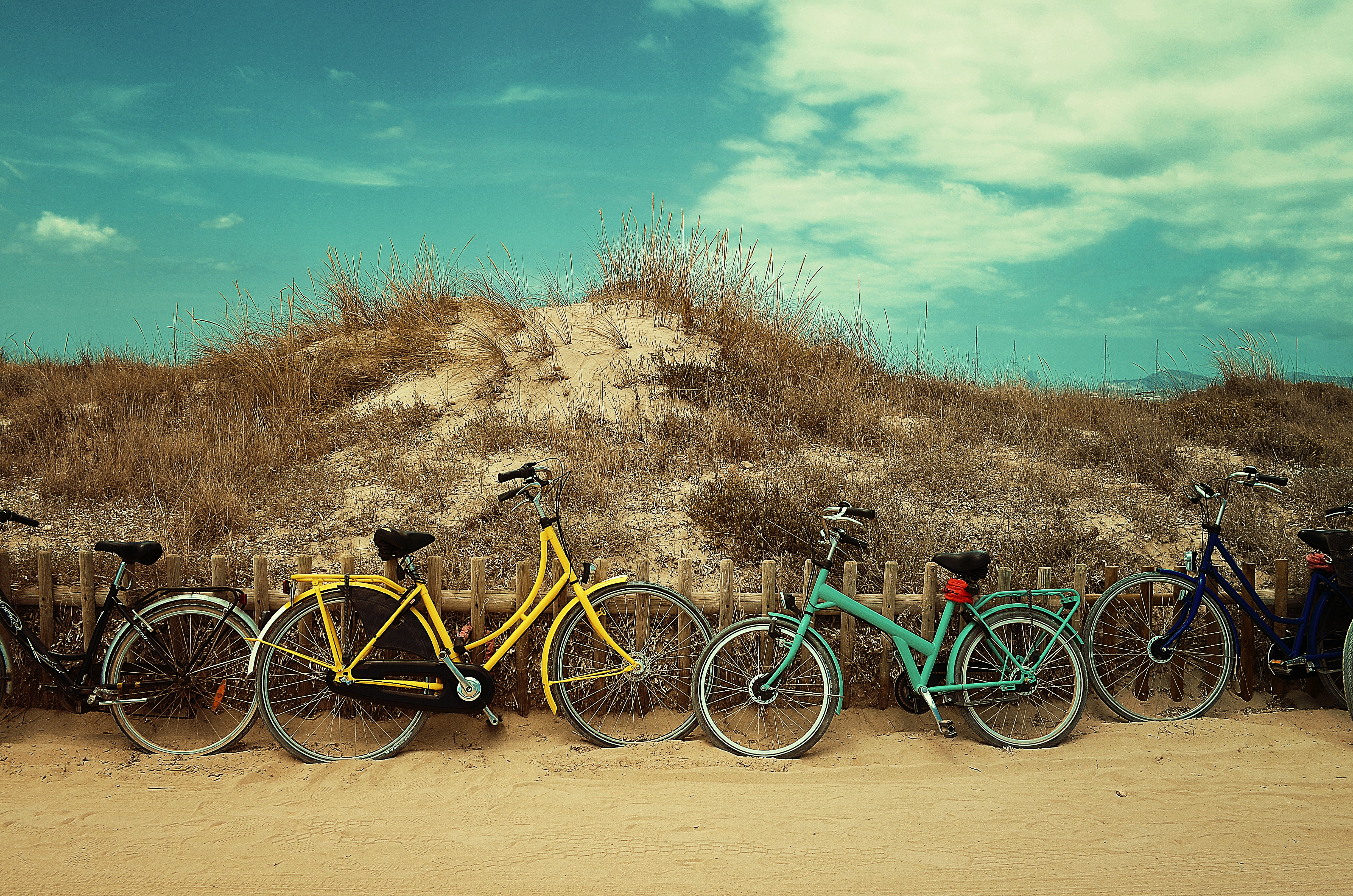Colorful bicycles leaned on a wooden fence at the Formentera beach