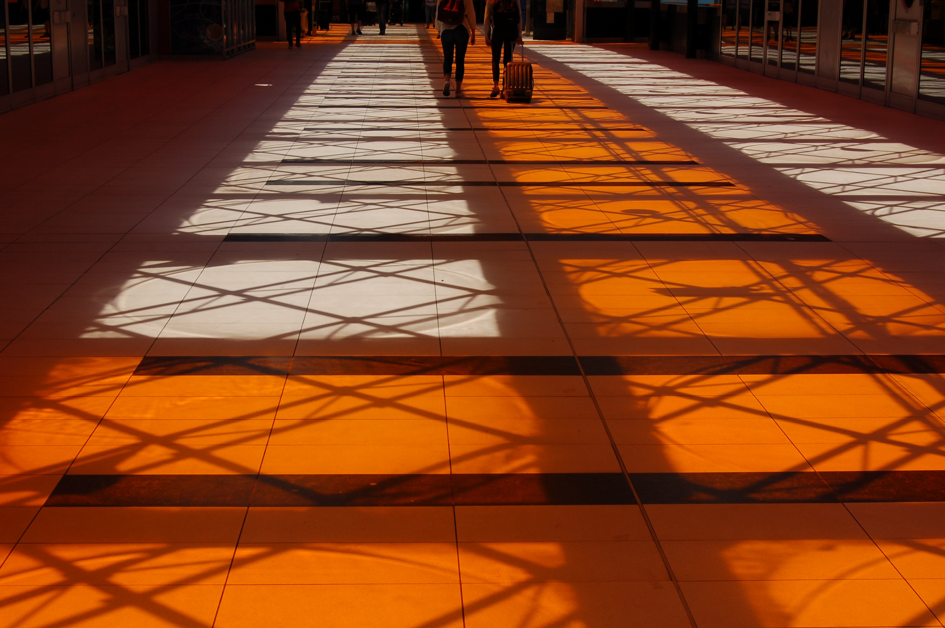 two person walking inside building with orange floor
