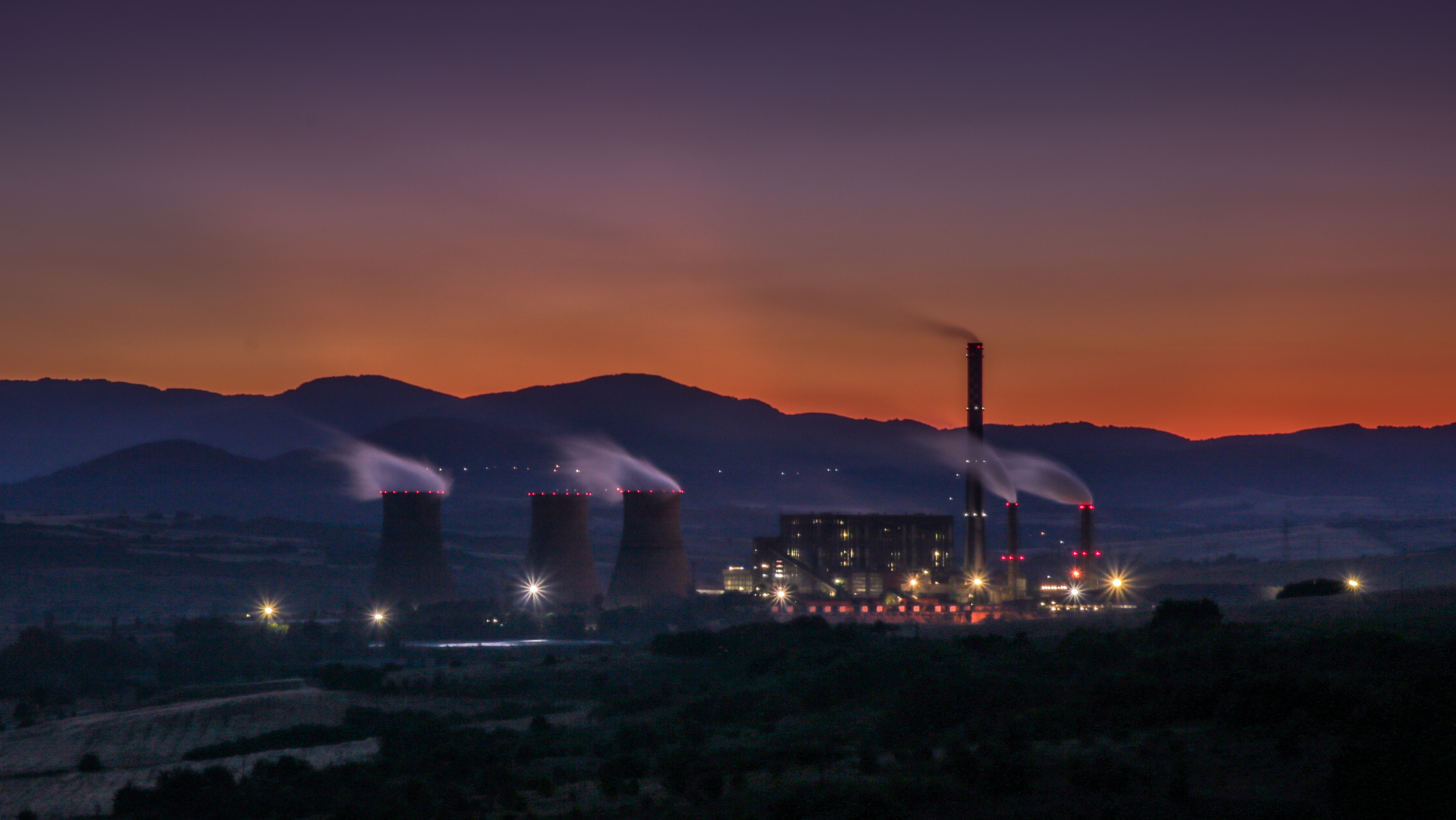 A full view of a thermal power plant with the sunset in the background