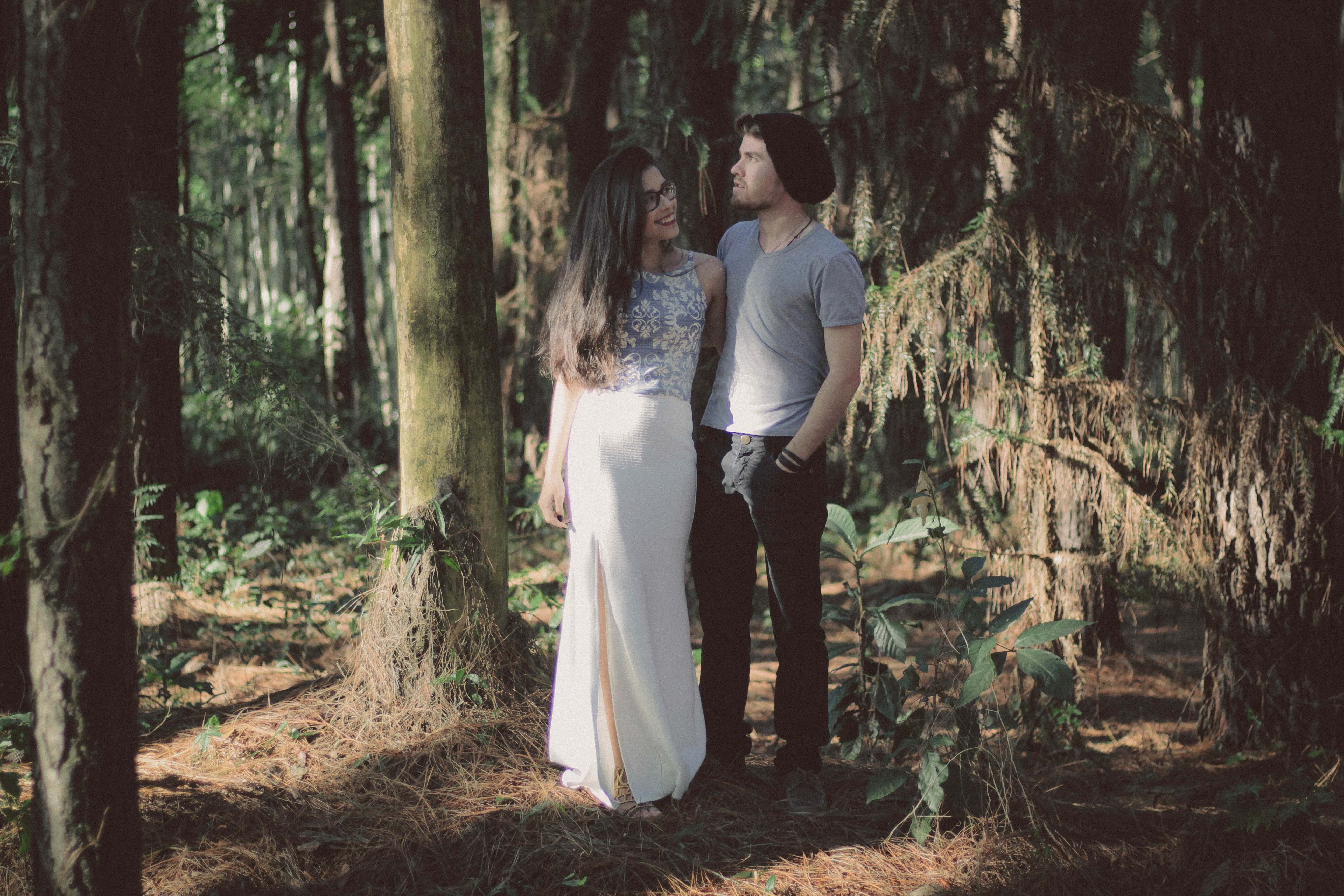 man and woman standing together surrounded by green trees and plants during daytime