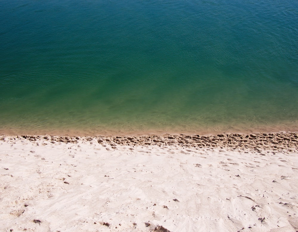 white sand near green calm body of water at daytime