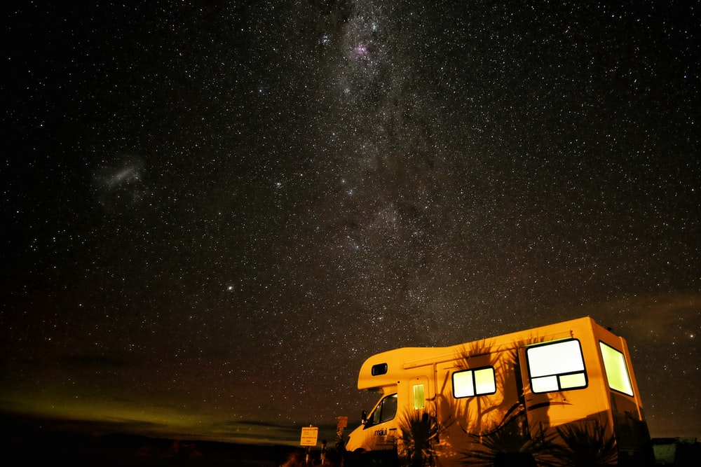 photo of white and brown vehicle during night time with stars