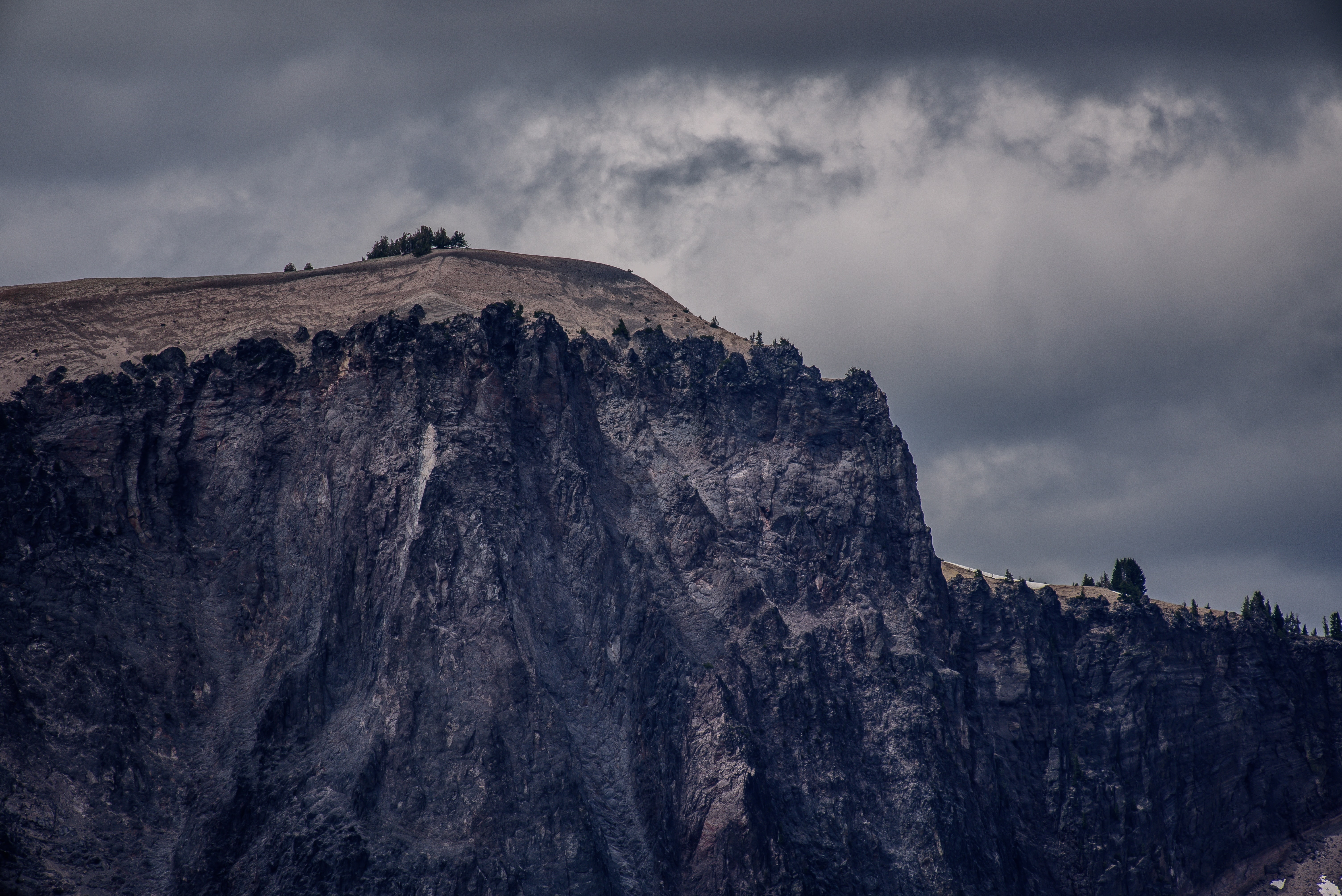 A mountain cliff in the clouds on a gloomy day at Crater Lake
