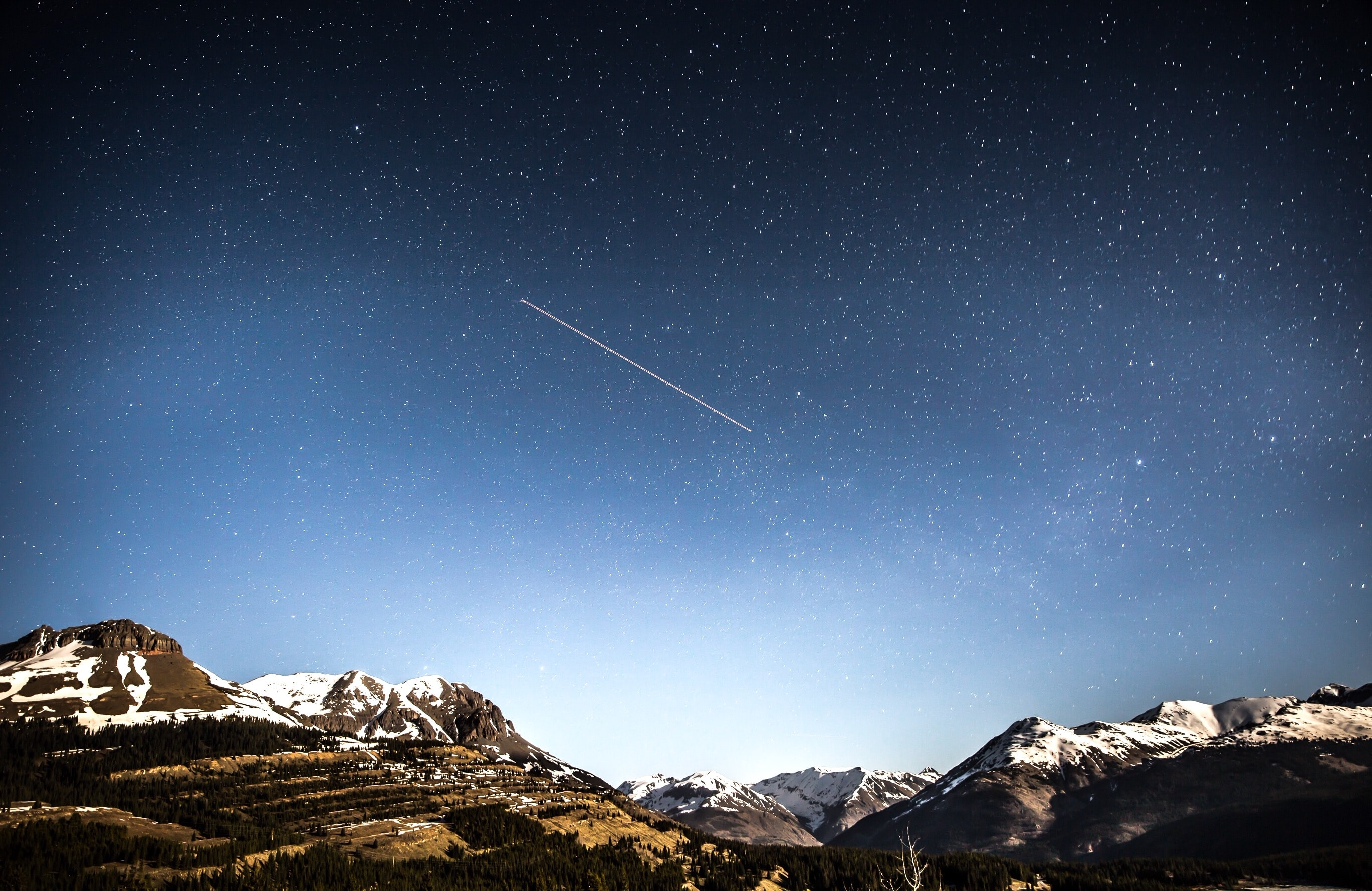 photo of shooting star over snow covered mountains