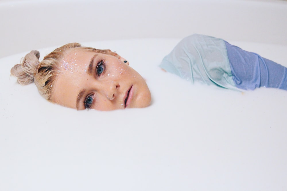 blonde hair woman in blue top on white liquid