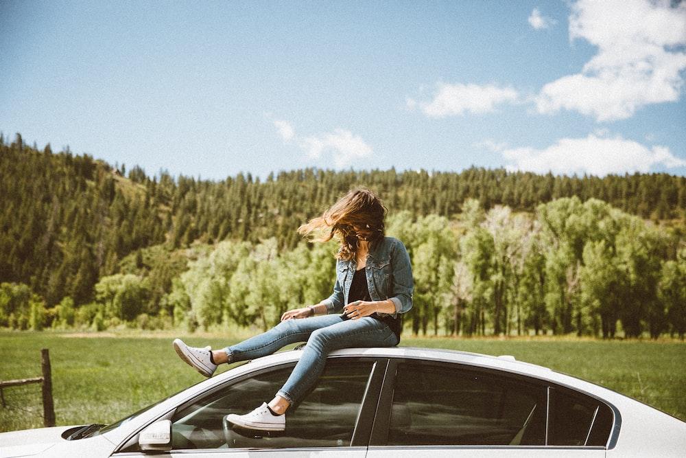 woman sitting on roof of white sedan