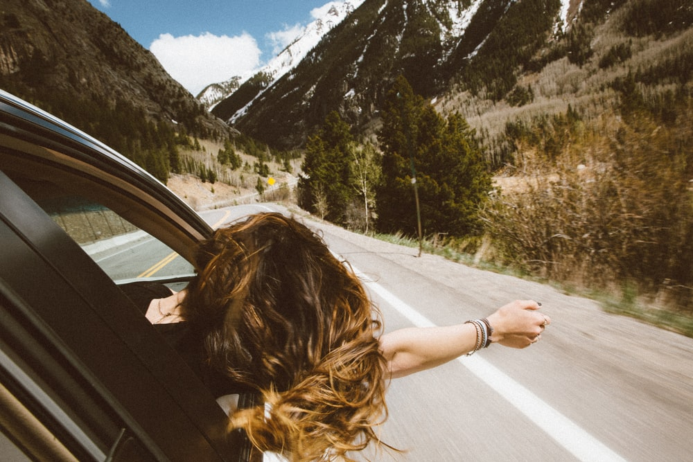 woman riding on vehicle putting her head and right arm outside the window while travelling the road