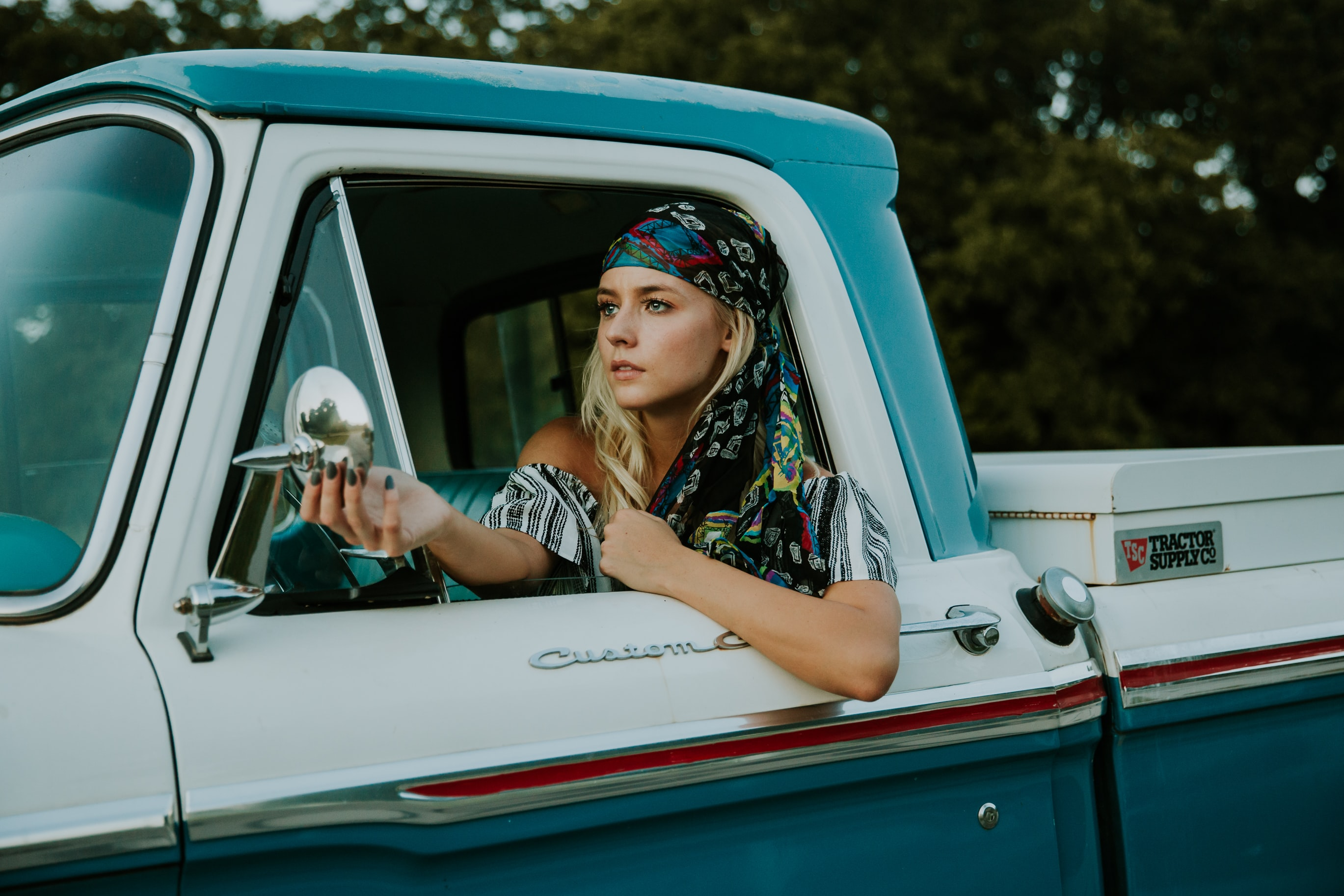 Attractive young blonde woman in bandana adjusting wing mirror of vintage pickup truck
