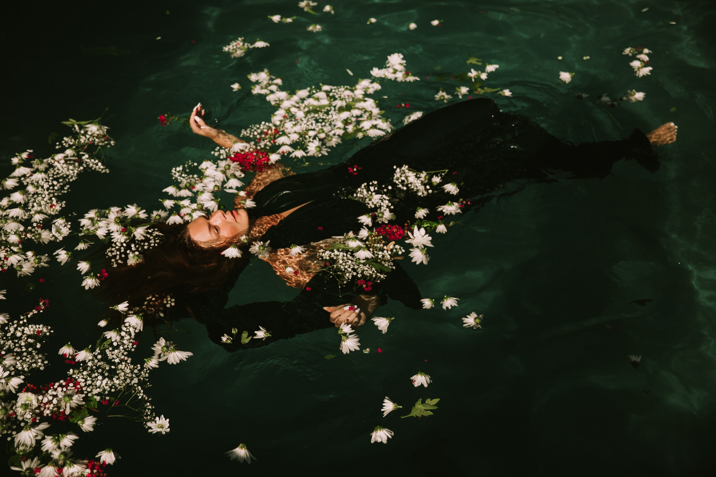 woman wearing black suit floats on the water