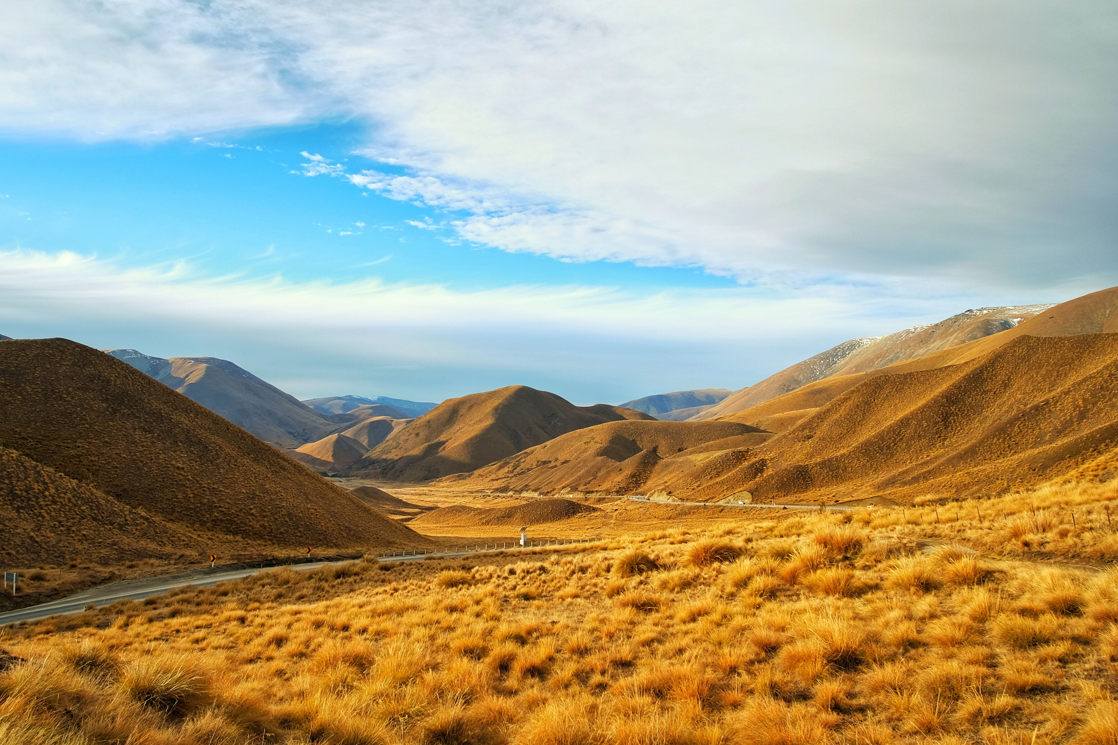 A road through undulating hills covered in golden glass