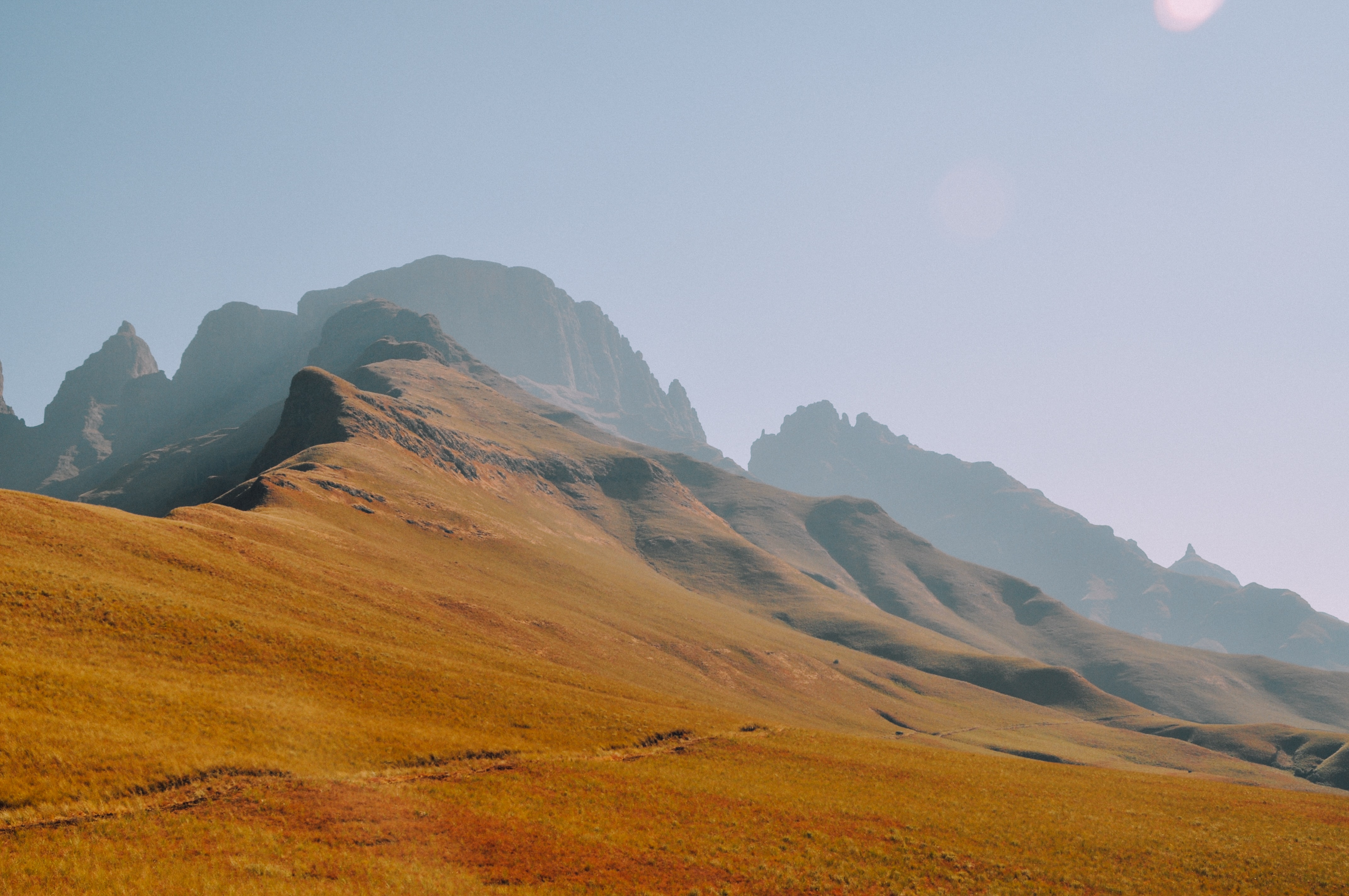 Ascent to a mountainous hill with orange, ocher ground on a cloudless day