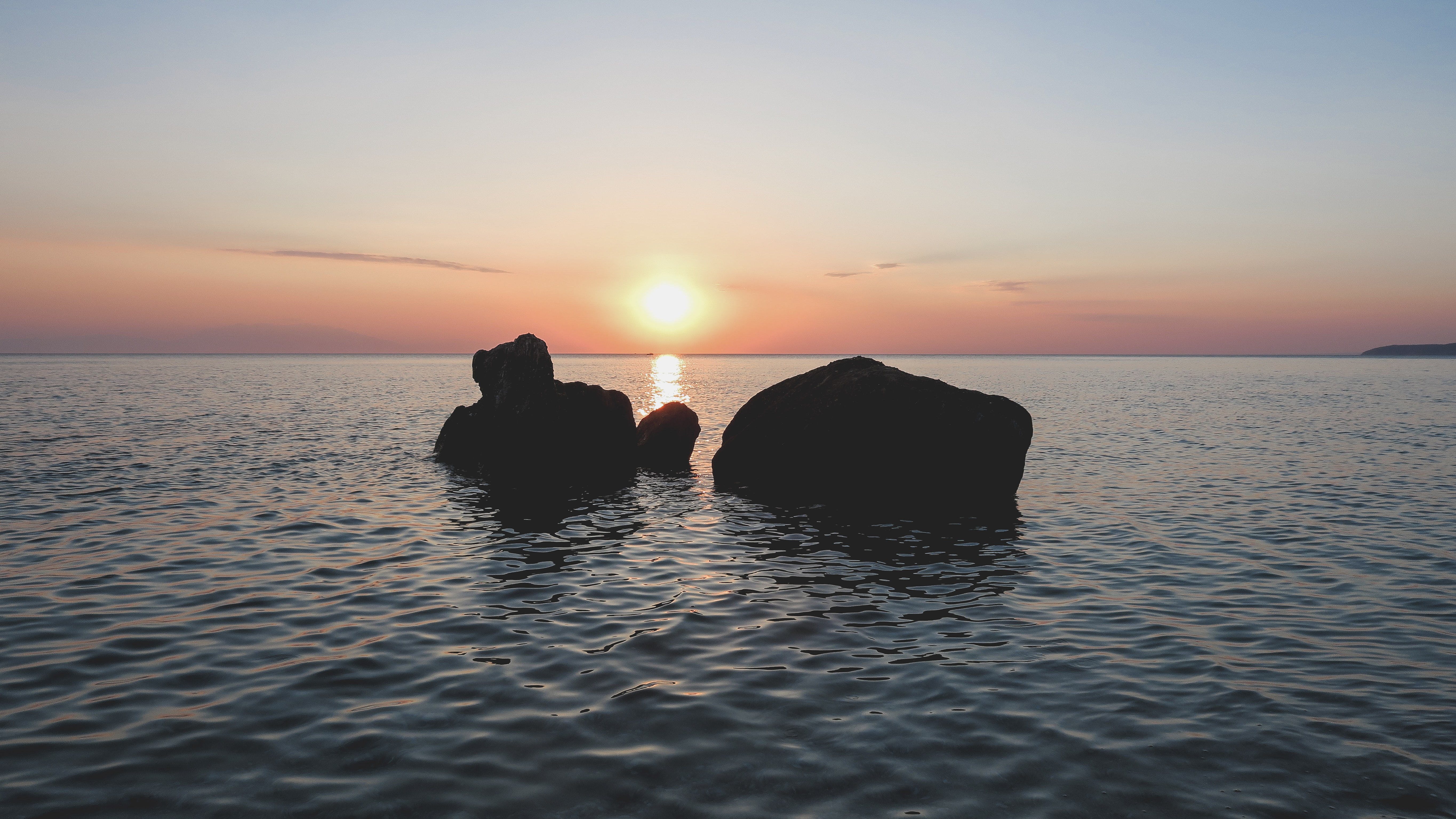 silhouette of rocks on body of water during golden hour