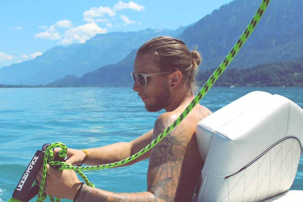 man holding black and green rope near body of water during daytime