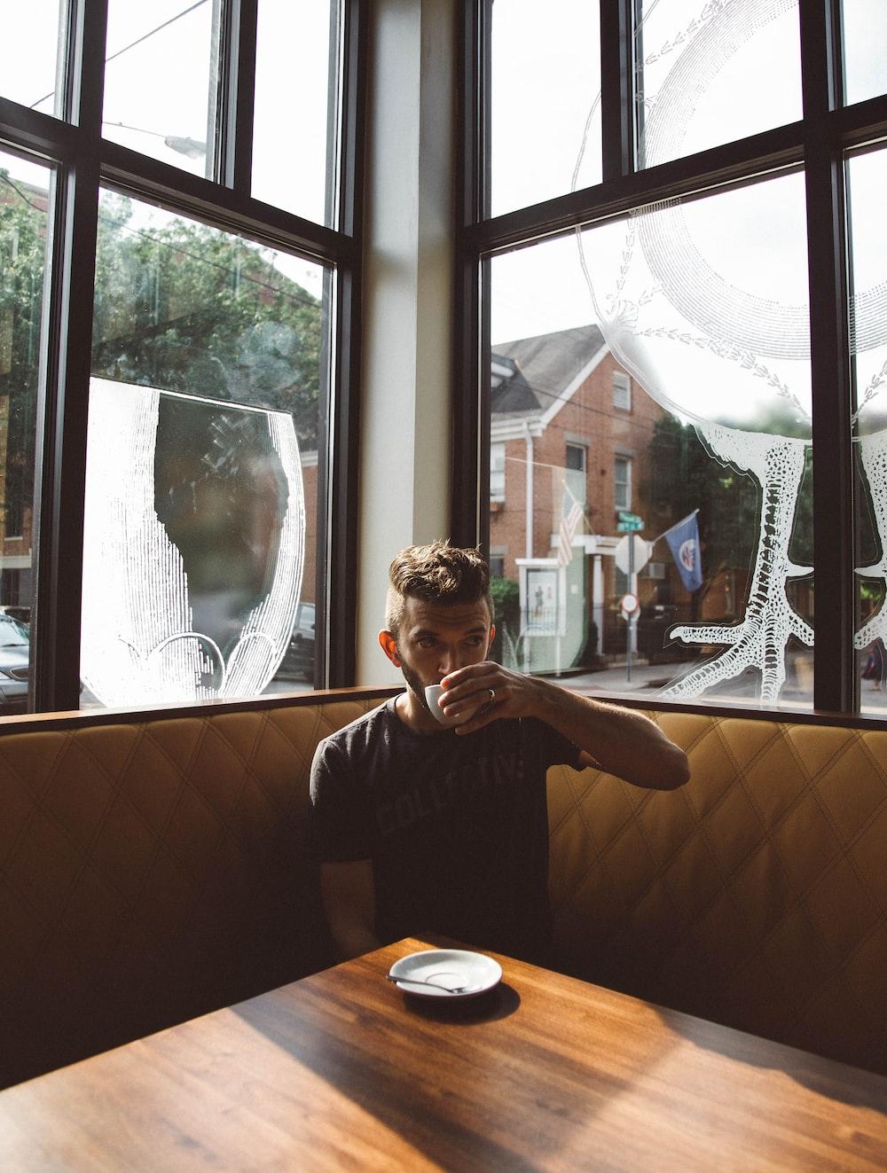 man sitting on brown sofa while drinking