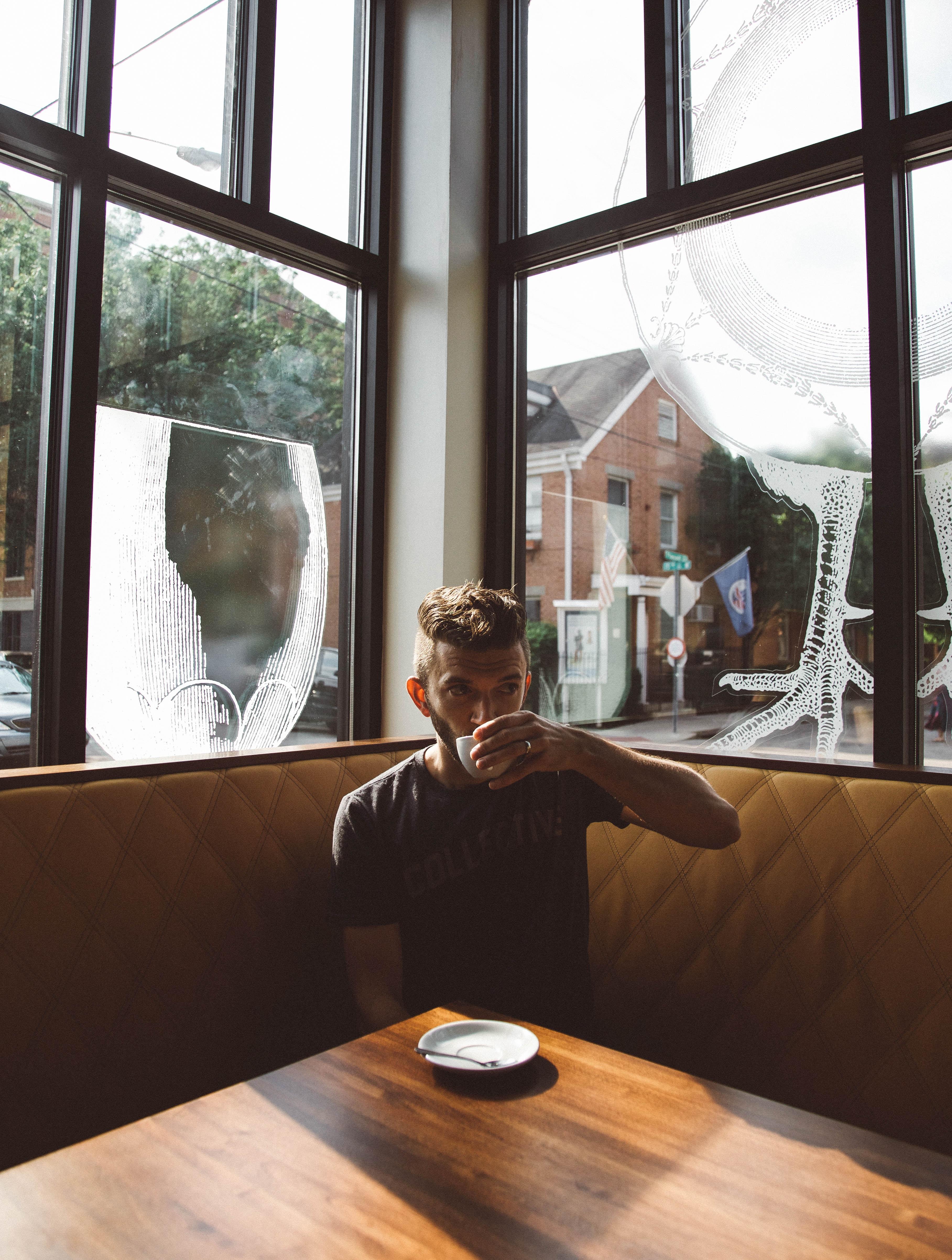 A man drinking coffee in the corner of a coffee shop in Cincinnati