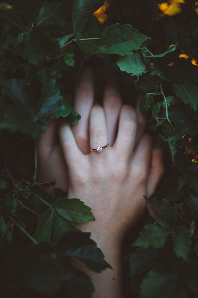 gold-colored ring on hands surrounded by green leaves