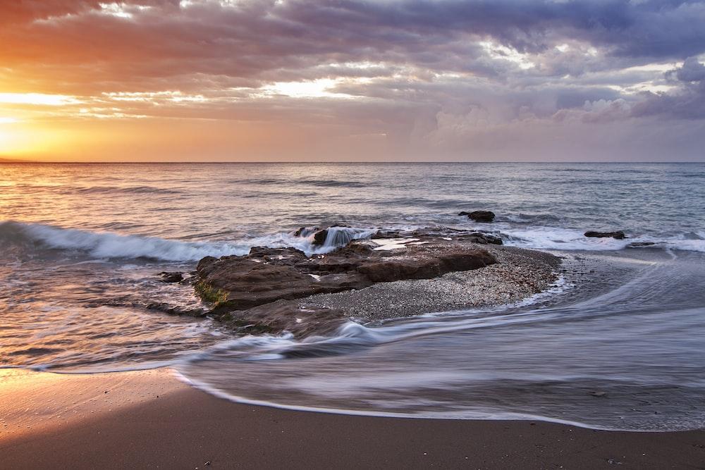 brown stone near seashore during sunset