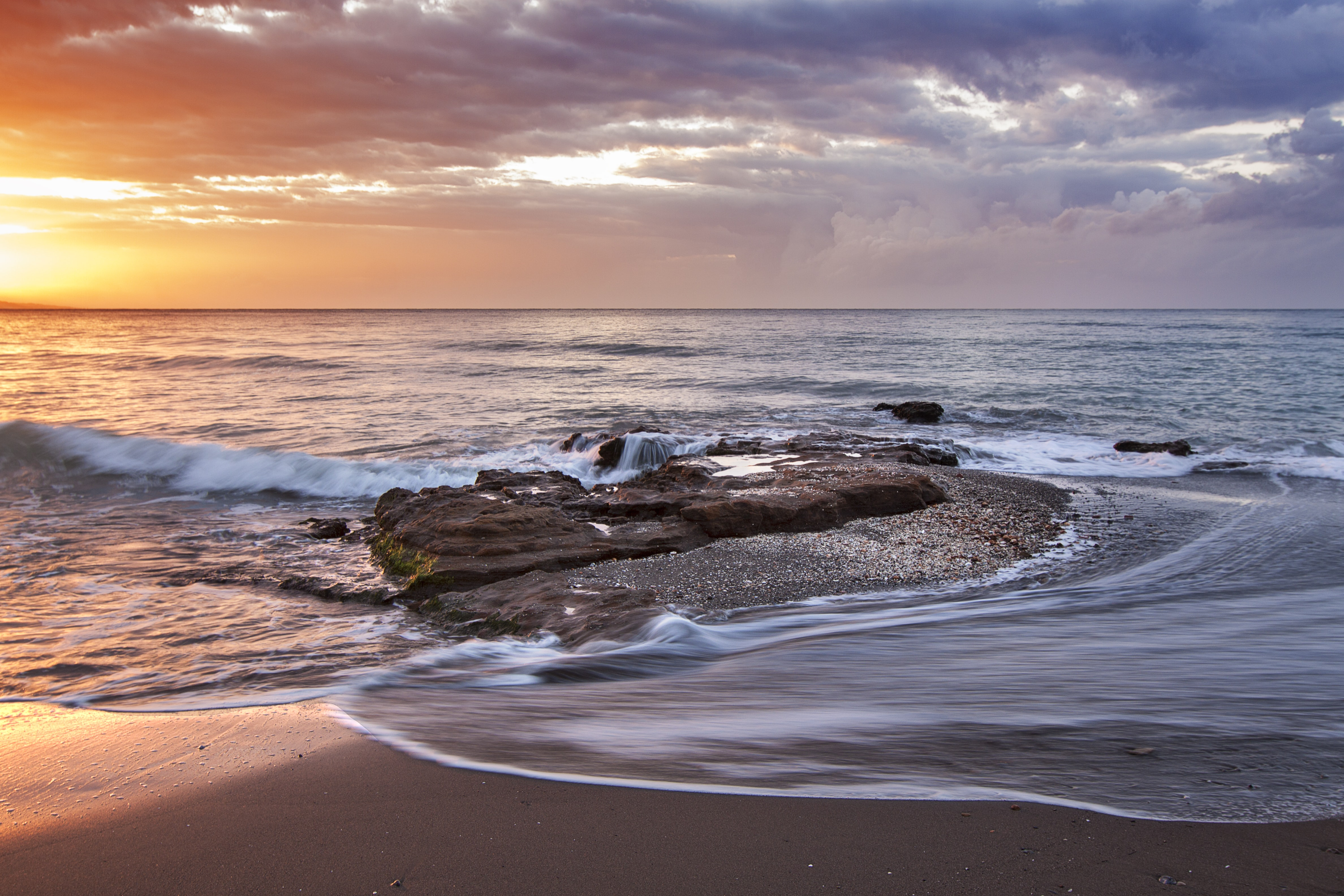 The ocean flowing onto the sandy beach under an orange, purple, and blue sky at sunset